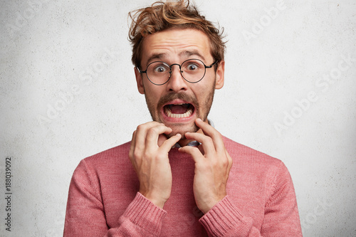Staande foto Kapsalon Worried scared fashionable man looks with terrified expression, keeps arms on chin, dressed in pink sweater, isolated over white background. Emotional bearded young guy receives unexpeted news