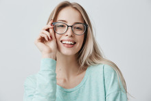 Cheerful Female Student In Stylish Eyewear Rejoices Successfully Passed Exams, Glad To Have Meeting With Groupmates. Delighted Beautiful Pleased Woman Has Attractive Look, Poses Indoors.