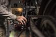 Close-up of mechanic fixing a motorbike