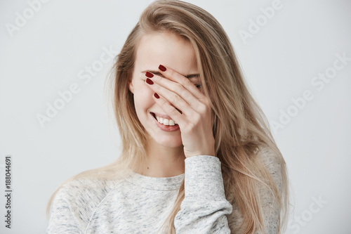 Fototapety, obrazy: Good-looking emotional young Caucasian woman with blonde long hair, closing eyes with hand while laughing out loud, happy with good positive news, smiling broadly, showing straight white teeth