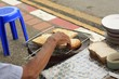 Old Thai man toasting bread on an open coal fire