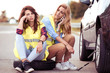 Two girls on the road trying to fix their car.