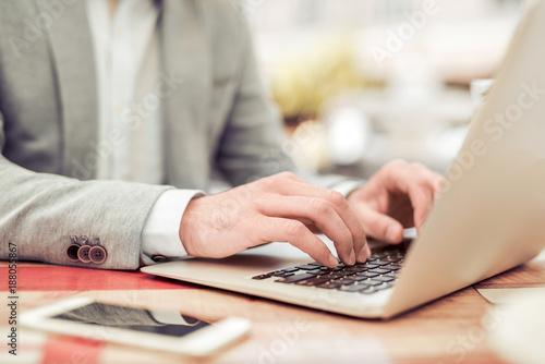 Fototapeta Young man using his laptop,close up. obraz na płótnie