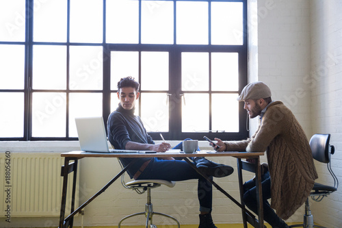 Side view of two entrepreneurs sitting and working at table in office.