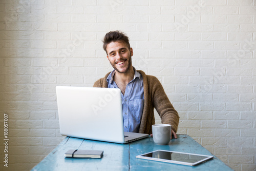 Cheerful young office worker looking at camera and sitting at laptop.