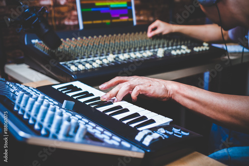 Fotografía male musician playing midi keyboard synthesizer in recording studio, focus on ha