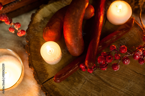 Delicious dinner in Ukrainian style sausage and cheese on hemp by candlelight looks very appetizing © Alla