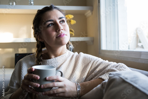 Daydreaming young pretty woman sitting and resting with cup on sofa.