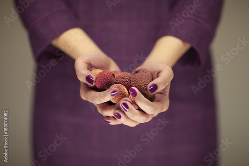 woman in violett 50's dress hands holding some lichees, sensual studio shot can be used as background
