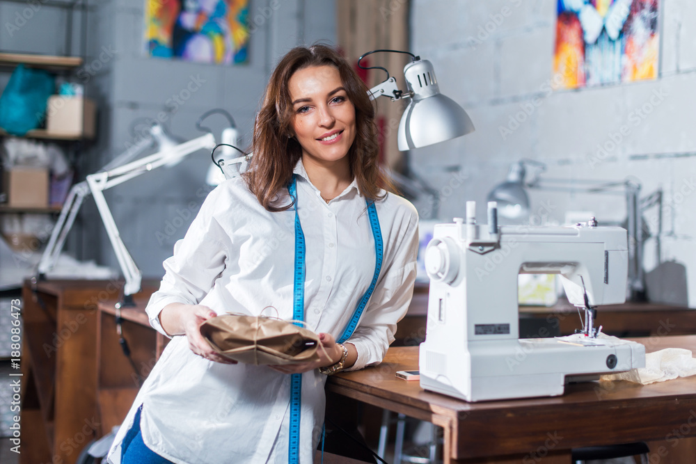 Fototapeta Portrait of smiling European fashion designer standing next to sewing machine holding a gift packed in craft paper in studio