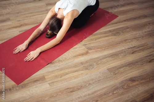Poster  Woman doing the Child's pose on red yoga mat. Balasana
