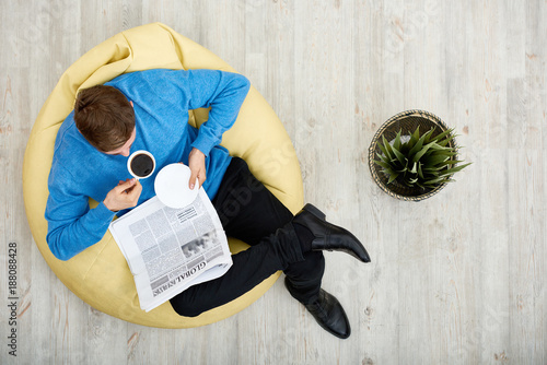 Directly above view of young man wearing blue sweater sitting on cozy beanbag ch Canvas Print