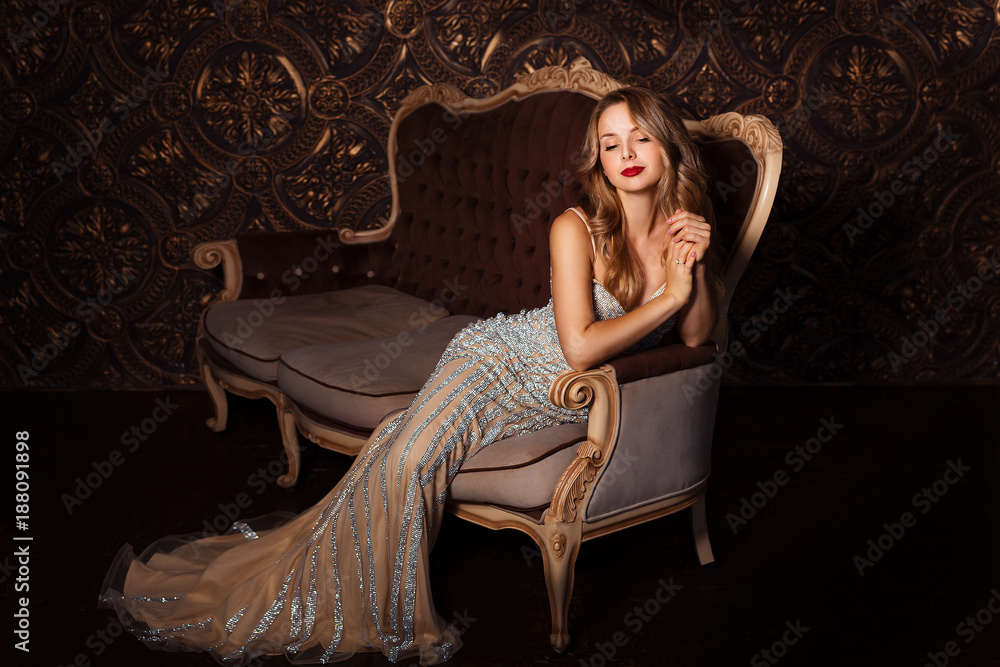 Fototapeta Fashion portrait of attractive woman in elegant dress posing indoors in sensual way