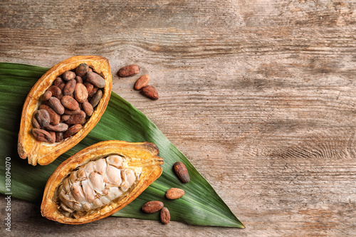 Fotografía  Cut cocoa pod with beans and tropical leaf on wooden background, top view