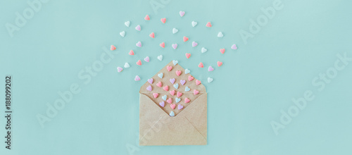 Multicolor sweets sugar candy hearts fly out of craft paper envelope on the light blue background . Valentine day. love concept. Gift, message for lover. Space for text. Wide banner.