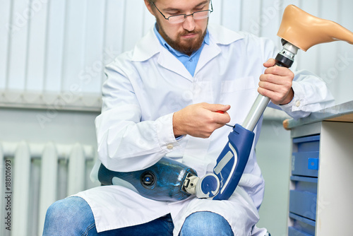 Portrait of bearded technician checking artificial limb while sitting at desk in Wallpaper Mural