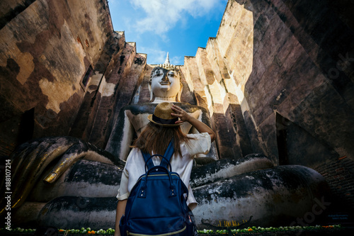 Fotografie, Obraz  Young woman traveler travelling into Big buddha statue at Wat Si Chum or Wat Sri Chum temple in the Sukhothai Historical Park contains the ruins of old Sukhothai, Thailand, UNESCO world Heritage Site
