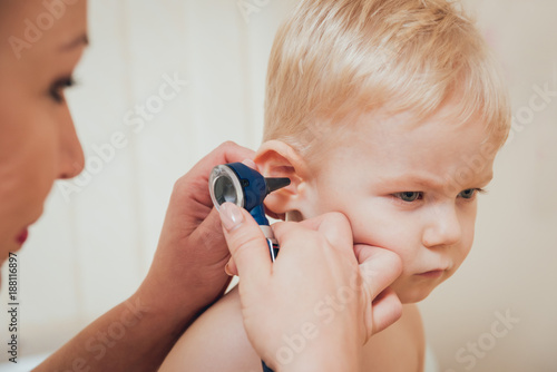 Photo Doctor examines ear with otoscope in a pediatrician room.