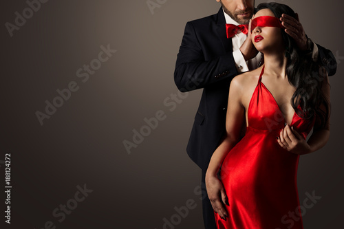 Fototapeta Couple Love Kiss, Sexy Blindfolded Woman Dancing in Red Dress and Elegant Man in