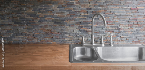 Fotografía  Wooden countertop with a modern stainless steel sink and faucet and a stone tile