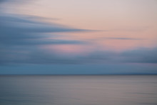 Sunrise Pink And Grey Clouds Over Silver Ocean Motion Blur