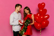 Attractive man gives red roses and making sweet present for her gorgeous girlfriend, dressed in red dress on St. Valentine's day.