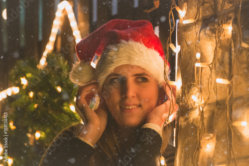 Poster Inspiration painterly Portrait of young female with Christmas decoration lights outdoors