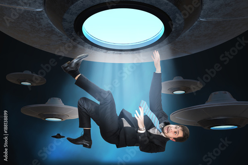 Alien abduction concept. Young man is abducted by UFO. Canvas Print