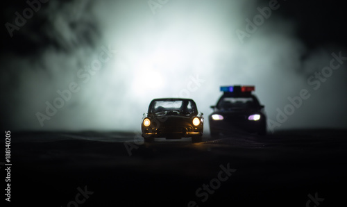 фотография  Toy BMW Police car chasing a Ford Thunderbird car at night with fog background