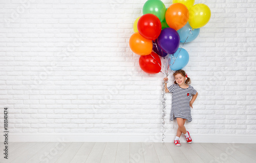 Fototapeta Happy funny child girl with  colorful balloons near an brick wall