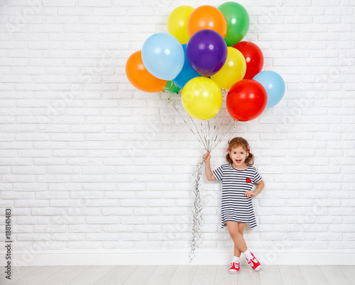 Fotografie, Obraz Happy funny child girl with  colorful balloons near an brick wall