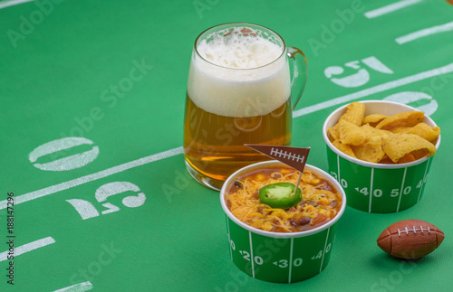closeup of chili and mug of beer and football decorations on table for game day Canvas Print