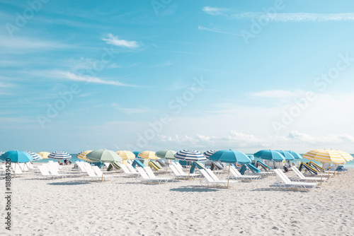 Sunny beach full of lounge chairs and umbrellas - 188149420