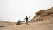 Following man running through the desert holding gimbal and camera as he records a vlog.