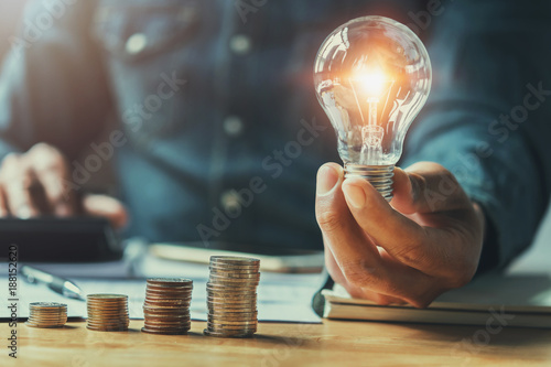 Obraz business man hand holding lightbulb with using calculator to calculate and money stack. idea saving energy and accounting finance in office concept - fototapety do salonu