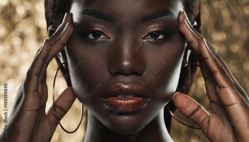 Fototapeta portrait of sensual young african woman against golden background
