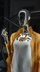 Metallic mannequin is dressed in white folded top and mustard-colored cardigan, dark background