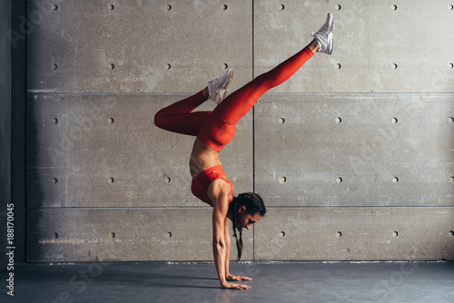 Obraz na płótnie Young fit woman doing handstand exercise in studio.