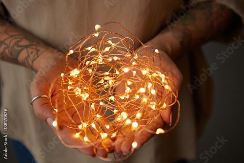 Fototapeta  Christmas lights garland in female hands