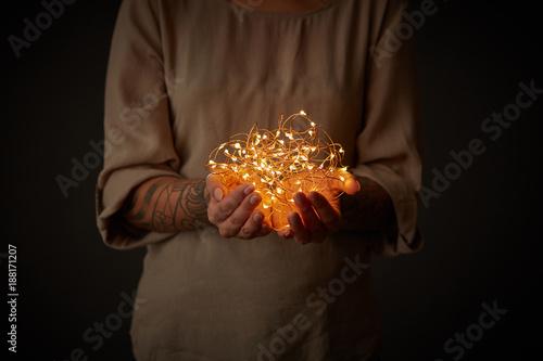 Obraz na plátně  Christmas lights garland in female hands