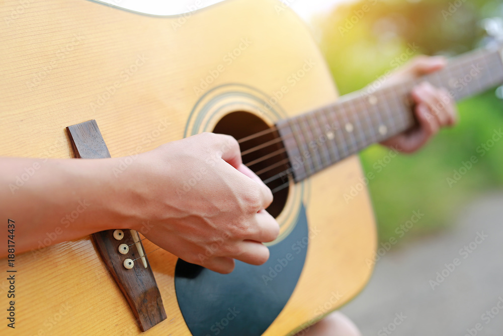 Valokuva Close-up male hands playing on acoustic guitar in the nature.