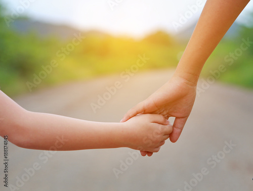 Fototapeta  Close up of Sister hold hands with small children walking on the road