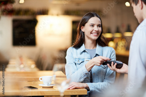 Fotografia Young smiling woman with card holding it over payment terminal while paying for