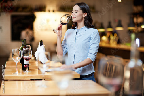 Modern sommelier estimating smell of red wine in wineglass at work