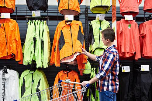 Plakat Mężczyzna wybiera odzież sportową w sklepie