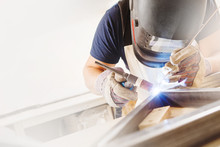 Male In Face Mask Welds With A...