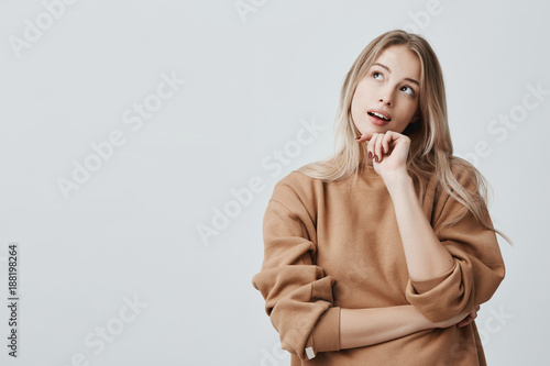 Fototapeta Portrait of pensive fair-haired dreamy hipster girl imagines something in her mind, looks upwards, being deep in thoughts, touching chin. Attractive young blonde female dreams about weekends obraz