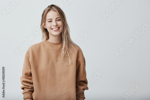 Fotografie, Tablou  Cheerful positive female youngster with blonde hair, dressed casually, glad to receive graduation congratulations from friends, starting new stage in life