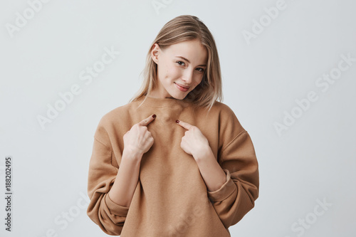 Fotomural  Shot of beautiful attractive blonde woman smiling, pointing with index fingers at herself, dressed in beige long-sleeved sweater, expressing positive emotions and feelings