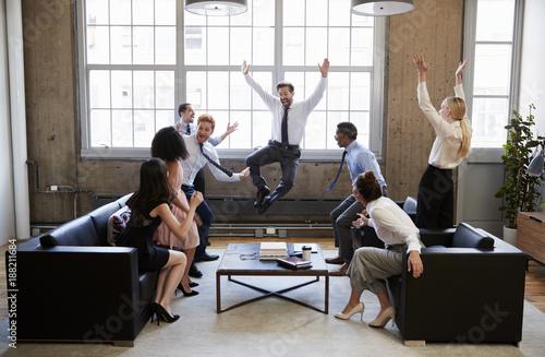 Fotografía  Business team jump for joy at hitting target in meeting